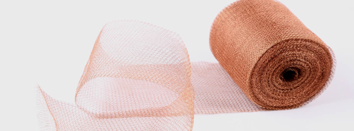 A roll of copper knitted mesh with a part opened on the gray background.