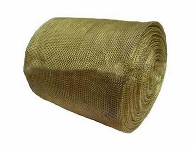 A roll of brass knitted wire mesh on the white background.