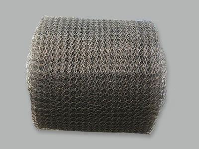 A roll of stainless steel knitted wire mesh on the white background.