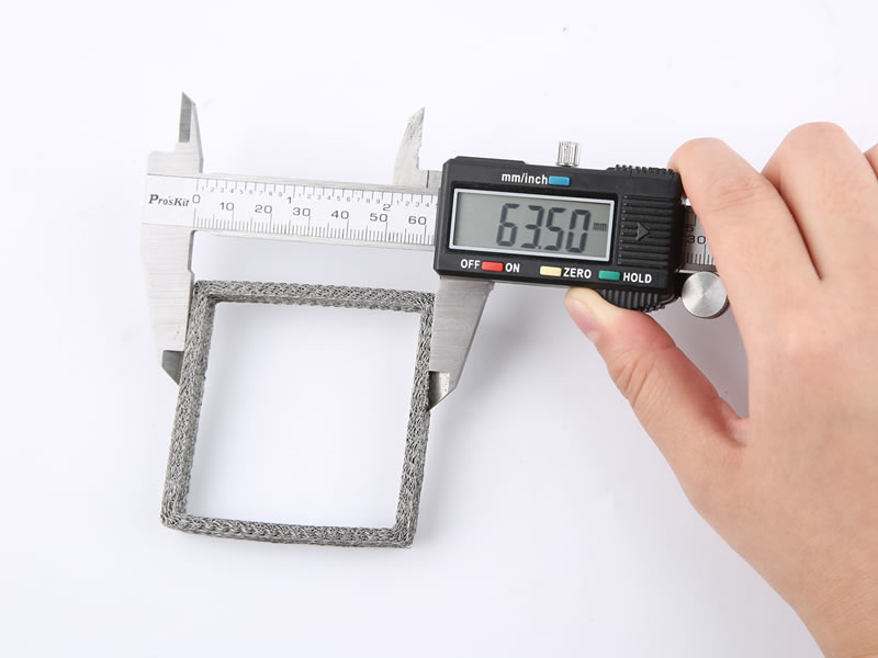 A hand is holding vernier caliper to measure outer diameter of hollow cylinder compressed knitted mesh.