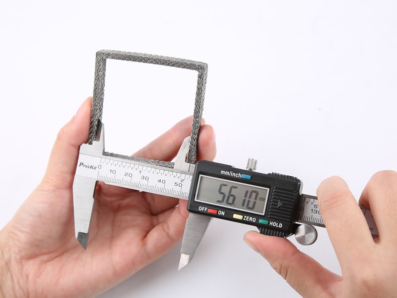 A hand is measuring inner length of saure compressed knitted mesh gasket with vernier caliper.