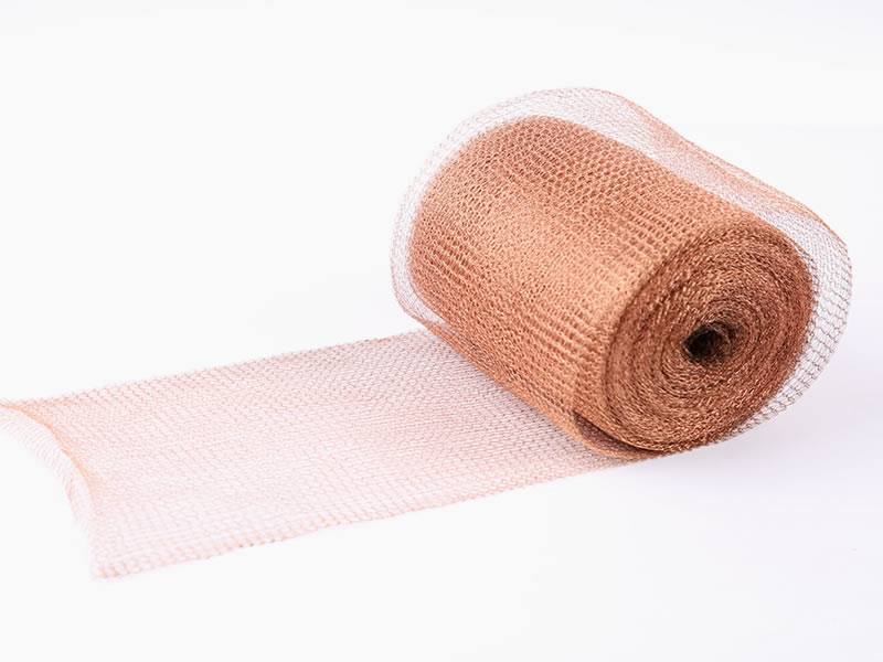 A roll of copper knitted mesh on the white background.