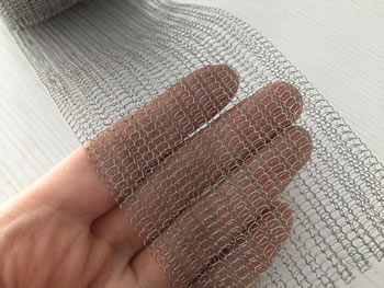 A piece of flattened knitted mesh in a woman's hand.