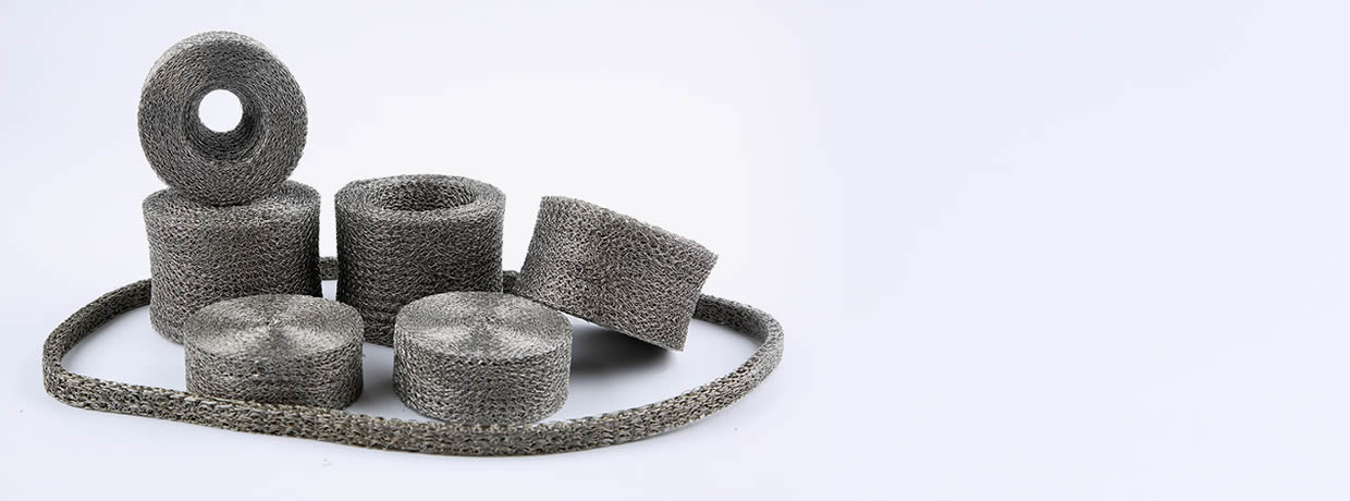 Several different shapes and specs of compressed knitted mesh on the gray background.