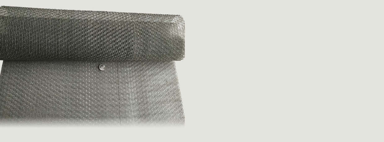 A roll of stainless steel knitted mesh fabric with a metal coin on its stretching part is on the floor.