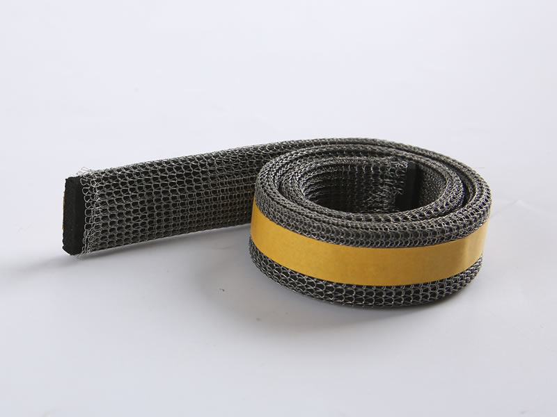 A roll of knitted mesh gasket with yellow color adhesive.