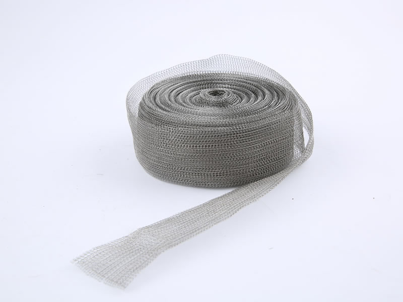 A roll of stainless steel knitted mesh on the white background.