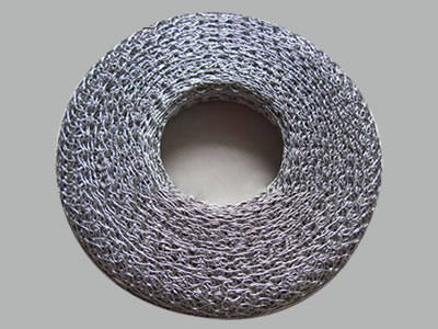 A circular shape compressed knitted mesh gasket on the gray background.