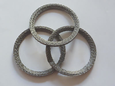 Three ring shape compressed knitted mesh gaskets on the gray background.