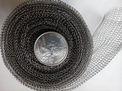 A small roll of stainless steel knitted mesh with a metal coin in the roll core.