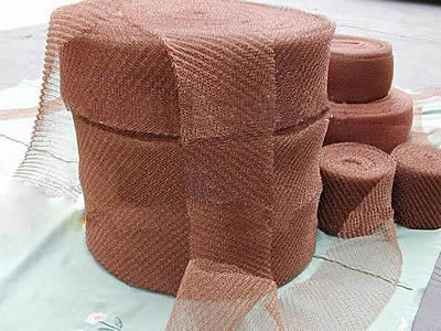 Several rolls of copper ginning knitted meshes on the white background.