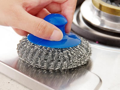 A hand is cleaning the gas cooker using knitted cleaning ball.
