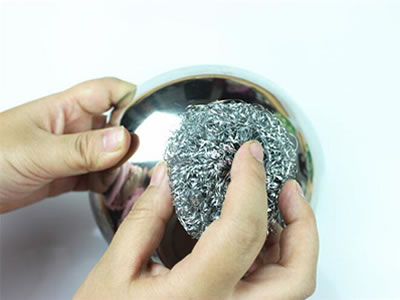 A hand is cleaning the bowl by the stainless steel knitted cleaning ball.