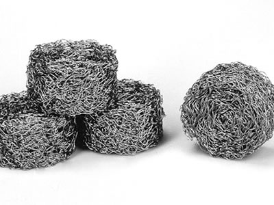 Four round compressed knitted wire meshes on the gray background.
