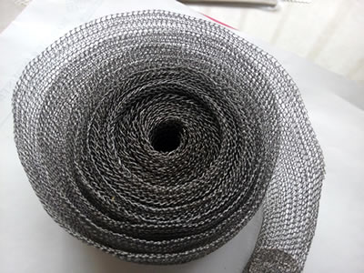 An unpacked knitted wire mesh tape on the white background.