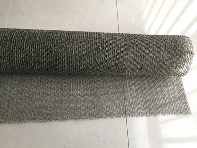 A big roll of stainless steel knitted mesh with a section stretching out.