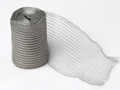 A roll of flattened stainless steel knitted mesh on the white background.
